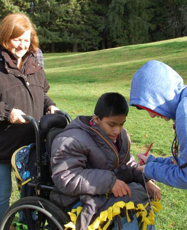 Outdoor school student in wheel chair having his wood cookie signed.