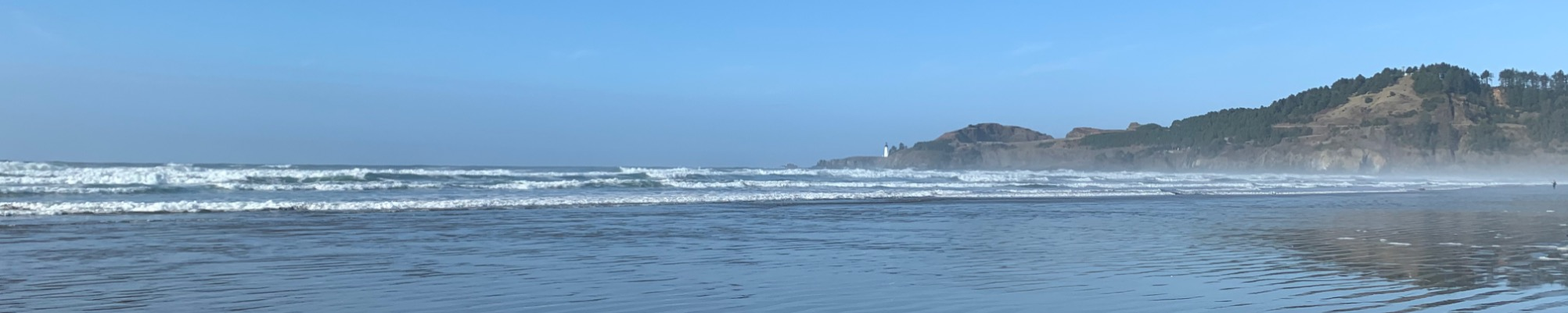 landscape photo of the Oregon coast, with blue sky, waves rolling into shore, and a long-distance view of Yaquina Head light house